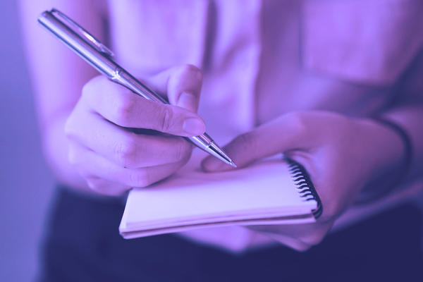 Photo of a woman writing on a pad with her fountain pen